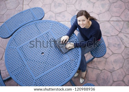 Beautiful female student working outdoors at school and smiling - stock photo