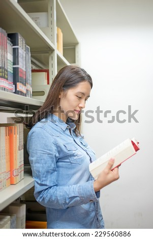 Beautiful female students reading in the library - stock photo
