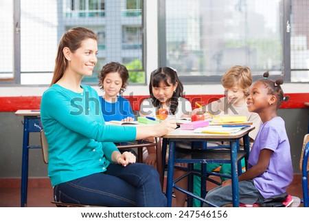 Beautiful female teacher smiling to her multi ethnic elementary classroom. - stock photo