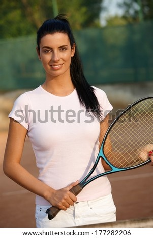 Beautiful female tennis player standing on tennis court, smiling.
