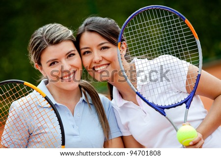 Beautiful female tennis players holding rackets and smiling - stock photo
