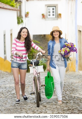 Beautiful female tourists walking together in a typical village - stock photo