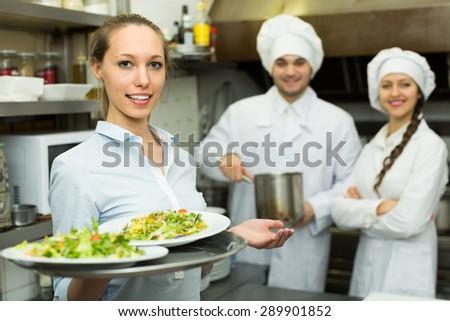 Beautiful female waiter taking dish from kitchen - stock photo