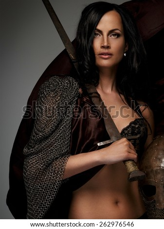 Beautiful female warrior holding sword and helmet - stock photo