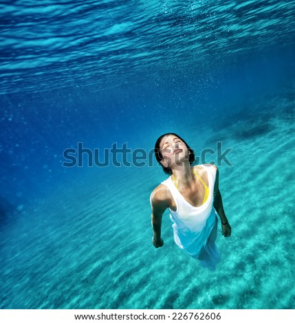 Beautiful female wearing white dress underwater, active lifestyle, swimming in clear transparent water of sea, summer vacation concept