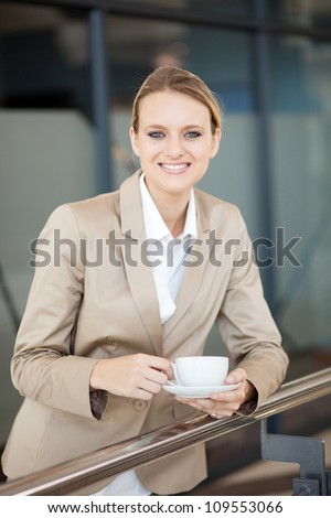 beautiful female white collar worker having coffee break at work - stock photo