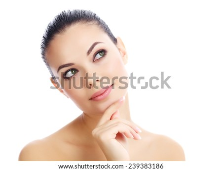 Beautiful female with clean fresh skin looking at something, white background - stock photo