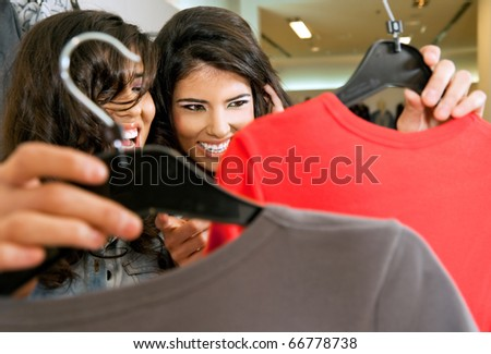 beautiful females holding hangers with clothes in fashion store - stock photo