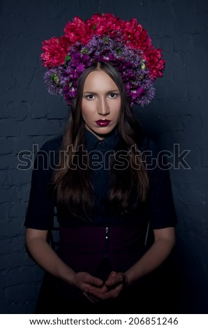 Beautiful femme fatale in dark clothes and a headdress from fresh colorful flowers