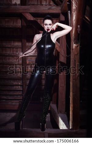 Beautiful fetish model with whip, seduction - stock photo