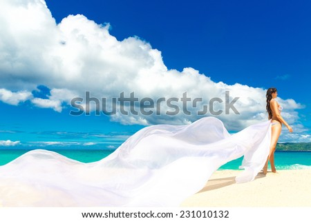 beautiful fiancee with big long white train, stand on shore sea - stock photo