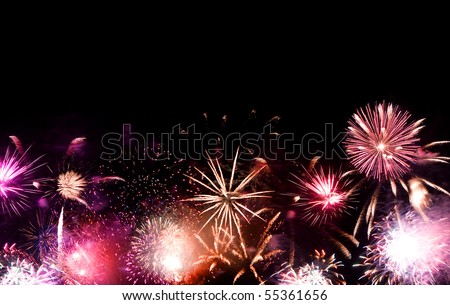 Beautiful fireworks going off with plenty of negative space in the dark night sky. - stock photo