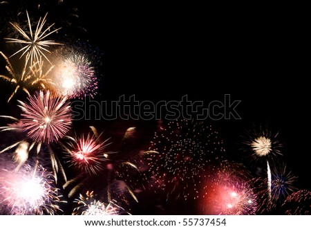 Beautiful fireworks going off with plenty of room for your text in the dark night sky. - stock photo