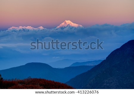 Beautiful  first light from sunrise on Mount Kanchenjugha, Himalayan mountain range, Sikkim, India. Blue coloured clouds surrounded the mountains at dawn  - stock photo