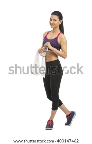 Beautiful fit female model holding a bottle of water, wearing towel and fitness clothing. - stock photo