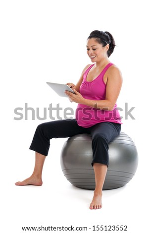 Beautiful fit Hispanic pregnant woman sitting on an exercise ball looking up information on pregnancy exercise on her tablet pc isolated on a white background - stock photo