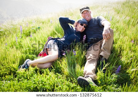 Beautiful fit Middle aged couple lying in the tall grass and Wild Lupine - stock photo