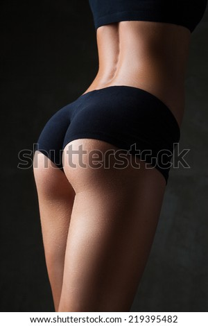 Beautiful fit, sexy female body on dark grey background - stock photo