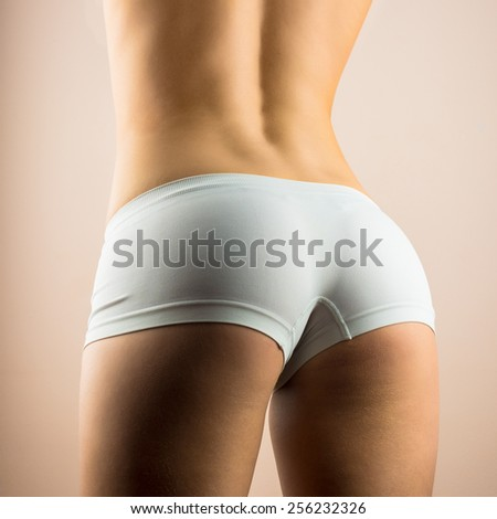 Beautiful fit sexy female body. the girl put on white shorts - stock photo