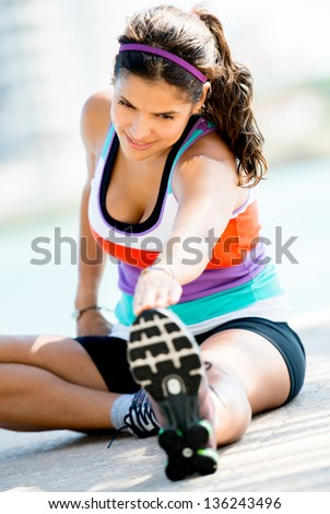 Beautiful fit woman doing stretches exercises outdoors - stock photo