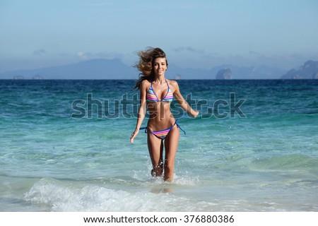 Beautiful fit woman in bikni run on tropical beach - stock photo