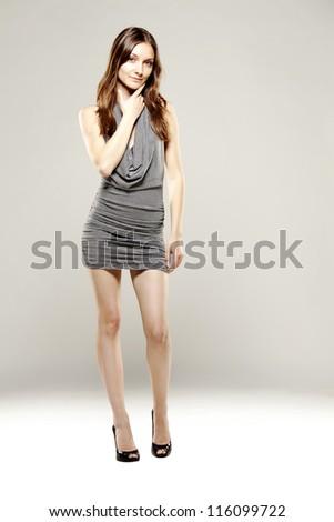 beautiful fit woman in fancy silver dress serious face for camera - stock photo