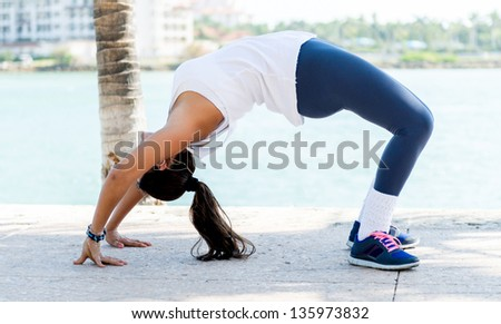 Beautiful fit woman stretching her back outdoors