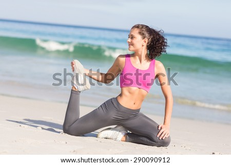 Beautiful fit woman stretching her leg at the beach