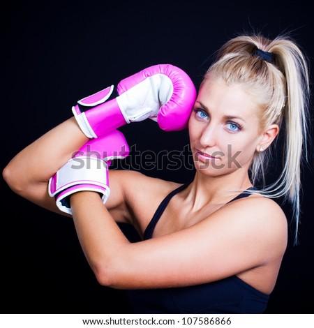 beautiful, fit woman wearing hot pink boxing gloves - stock photo