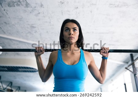 Beautiful fit woman working out with barbell at gym - stock photo