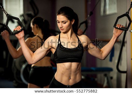 Beautiful fit woman works out in a fitness gym