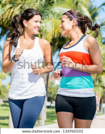 Beautiful fit women running outdoors and looking happy - stock photo