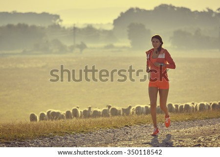 Beautiful fit young lady in red summer sportswear running, jogging on a country road while listening to music in earphones, early in the morning. Calories burning. Health care. Willingness concept. - stock photo