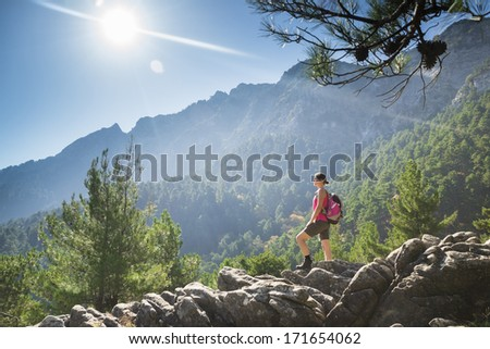 Beautiful fit young woman hiking up a mountain and enjoying at the view on the island of Thassos, Greece. - stock photo