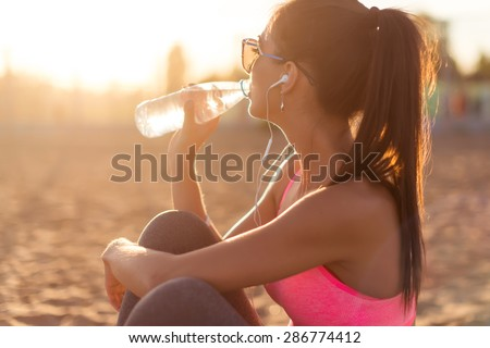 Beautiful fitness athlete woman drinking water after work out exercising on sunset evening summer in beach outdoor portrait - stock photo