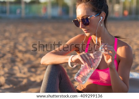 Beautiful fitness athlete woman drinking water after work out exercising on sunset evening summer in beach outdoor portrait. - stock photo