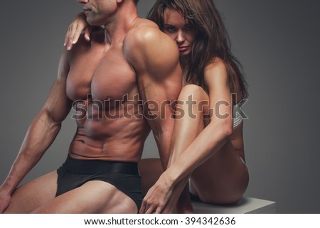 Beautiful fitness couple posing in a studio. - stock photo