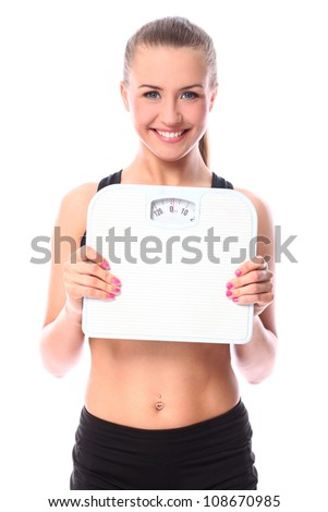 Beautiful fitness girl holding scales over white background