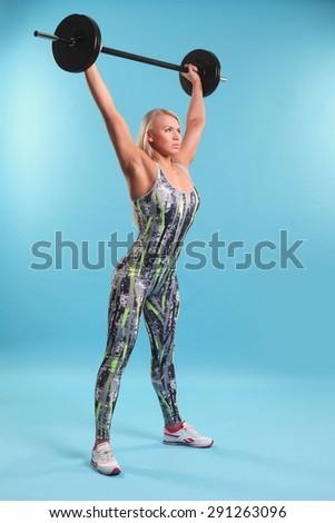 Beautiful fitness girl liftings weights. studio photo - stock photo
