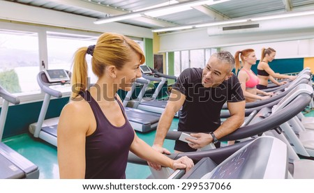 Beautiful fitness woman in a treadmill talking with handsome man on a fitness center - stock photo