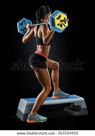 Beautiful fitness woman preparing to lift some heavy weights. Strong young woman with beautiful athletic body doing exercises with barbell. - stock photo
