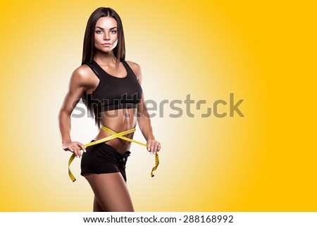 beautiful fitness woman with measure tape - stock photo