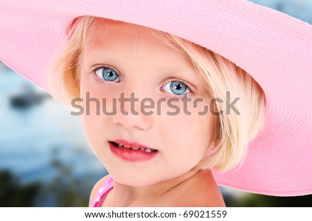 Beautiful five year old girl in big pink summer hat and blue eyes outside. - stock photo