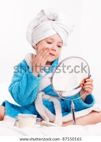 beautiful five year old girl with a mirror applying cream on her face on the bed at home - stock photo
