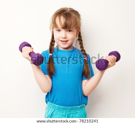 beautiful five year old girl working out with  dumbbells at home - stock photo