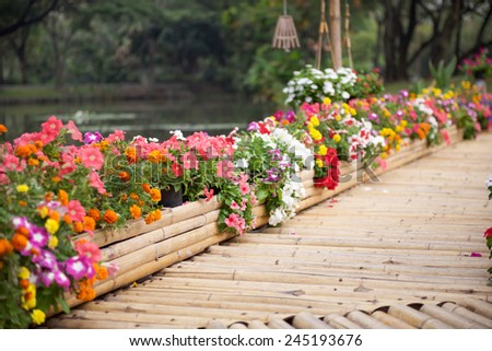 Beautiful flower garden with bamboo path - stock photo