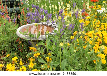 beautiful flower garden with colorful flowers and a bird bath - stock photo