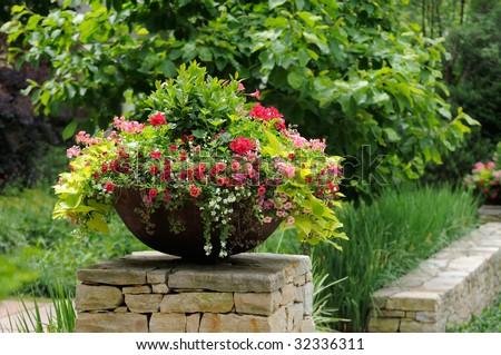 Beautiful flower pot with geranium, calibrachoa (million bells), sweet potato vine, framing house entrance - stock photo