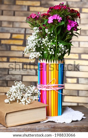 Beautiful flowers in colorful pencils vase on brick wall background