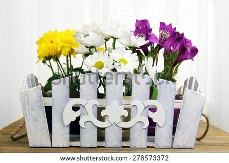 Beautiful flowers in ornamental flowerpot on fabric background - stock photo